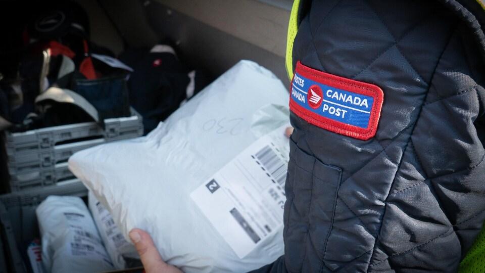 Un facteur de Postes Canada manipule un colis
