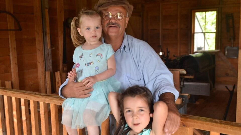 Un homme accompagné de deux fillettes.