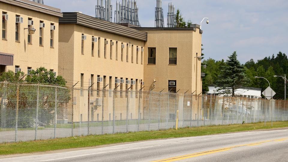 Une clôture de barbelés est installée devant le bâtiment du Centre de recherches à Valcartier, le long de la route de la Bravoure.