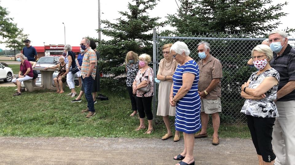 Des gens recueillis lors d'une cérémonie.