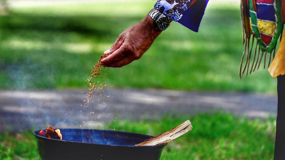 Une main lâche du tabac dans un réceptacle où brûle un feu.