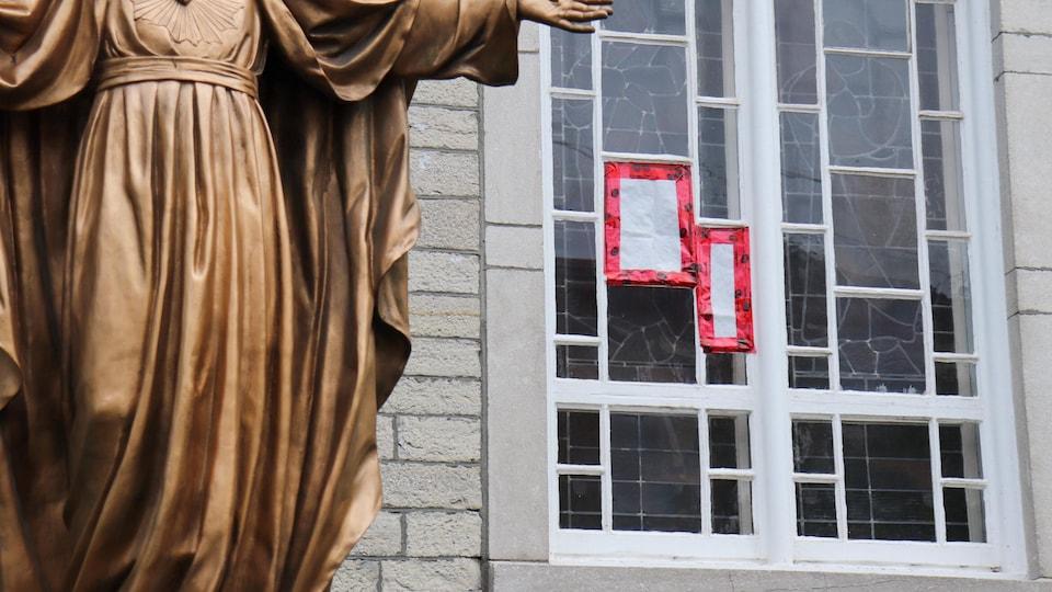 Une statue avec en arrière-plan une fenêtre brisée.