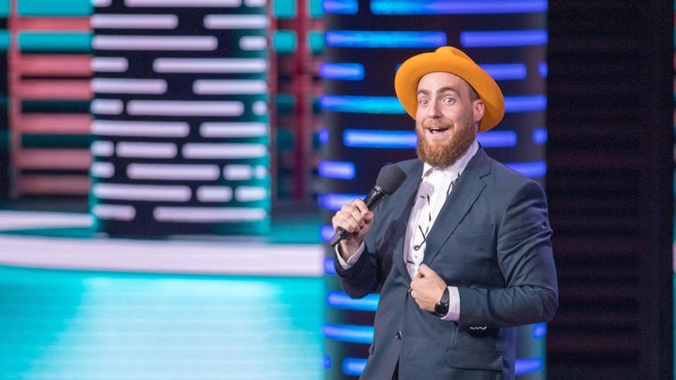 L'homme est sur scène et porte un chapeau.