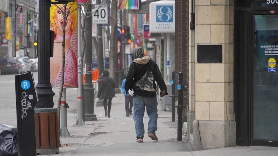 Un homme seul marche dans une rue de Montréal.