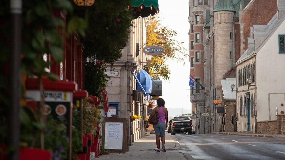 Une touriste se promène sur un trottoir vide du Vieux-Québec.