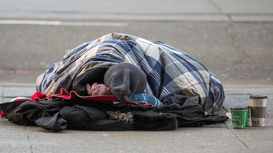 Une personne endormie dans un sac de couchage sur le trottoir.