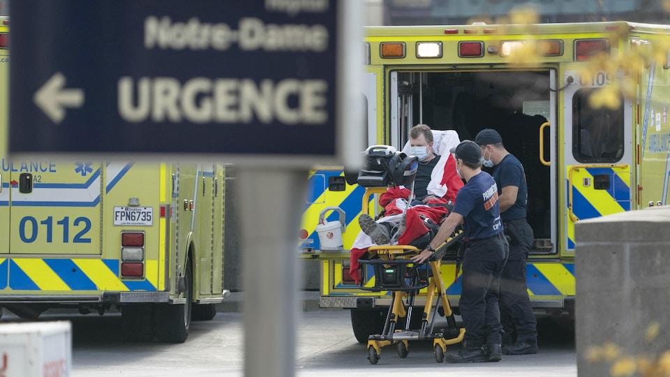 Deux techniciens ambulanciers descendent un patient sur une civière au sortir d'une ambulance.