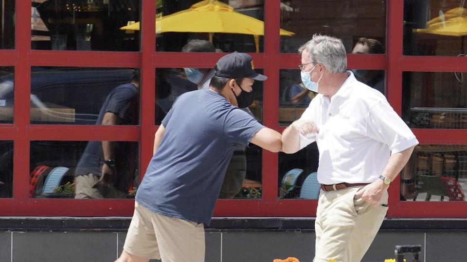 Le maire d'Ottawa donne un coup de coude amical à un serveur sur le bord d'une terrasse.
