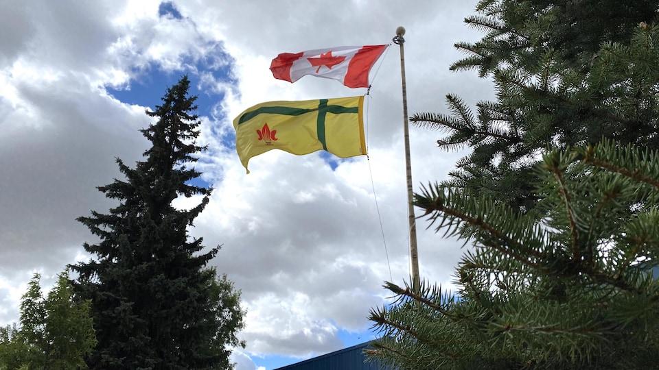 La drapeau canadien et le drapeau fransaskois flottent au vent.