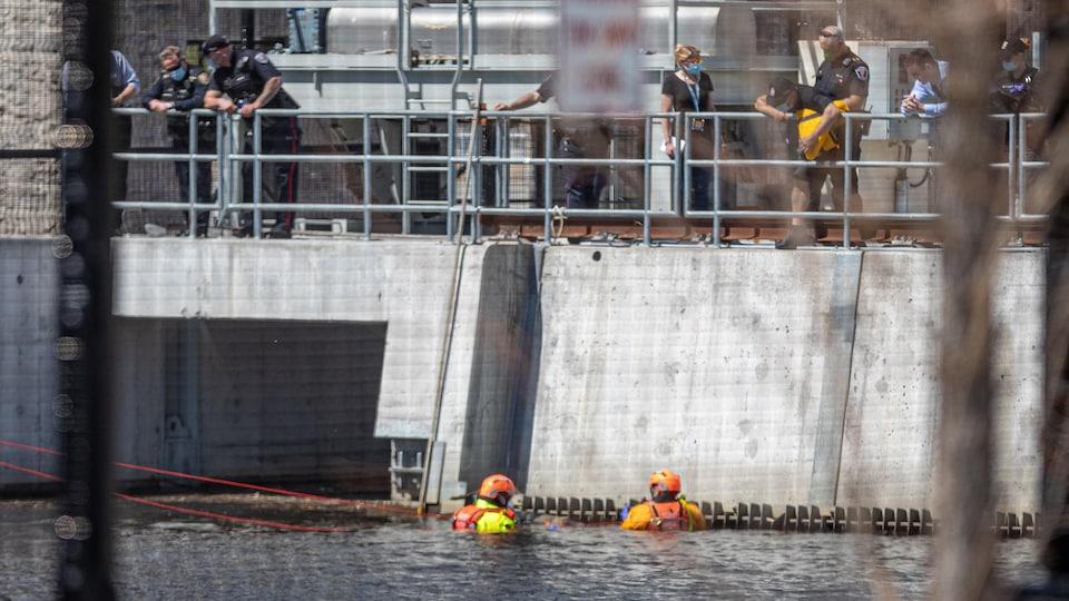 Deux personnes avec de l'équipement sont dans l'eau.