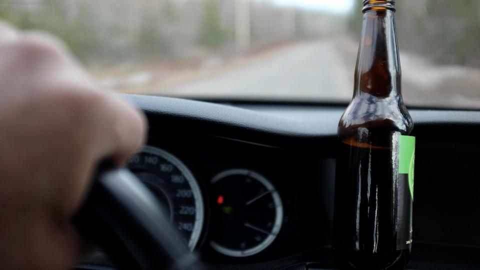 une bouteille de bière sur un tableau de bord de voiture