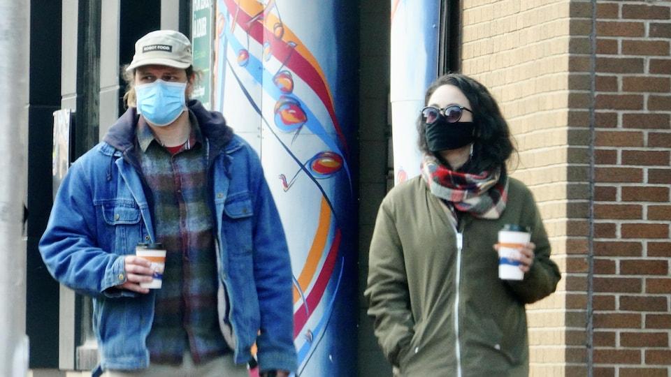 Des passants dans la rue, café à la main et masque sur le visage.