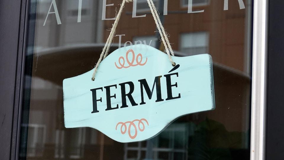 Un écriteau « fermé » suspendu à la porte vitrée d'un commerce le 4 février 2021 à Dieppe au Nouveau-Brunswick.