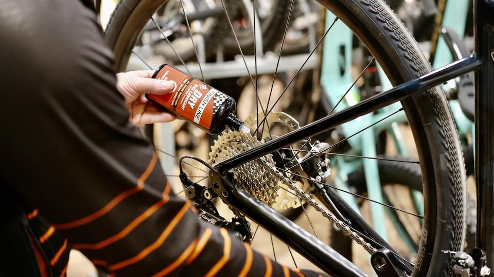 Une personne huile le pédalier d'un vélo.