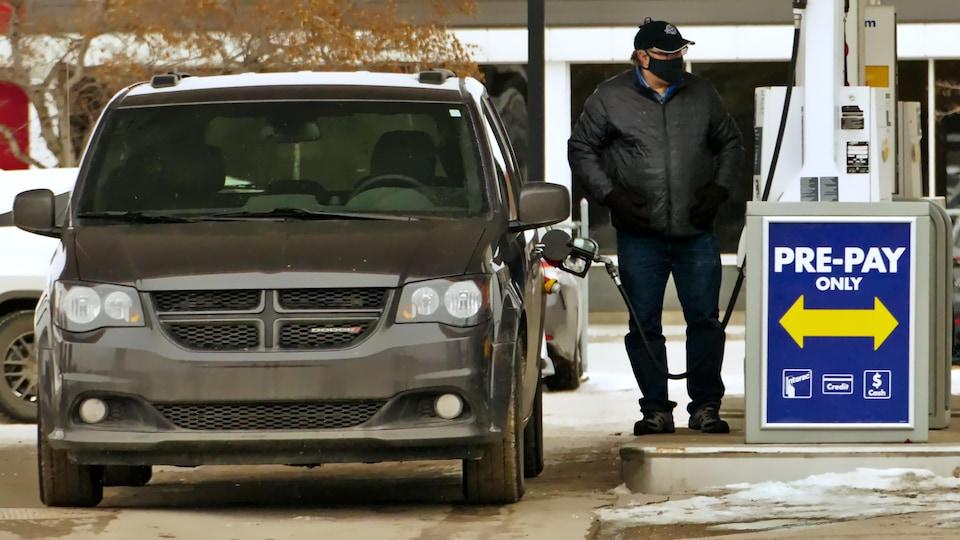 Un homme portant le masque à Regina met de l'essence dans sa voiture.