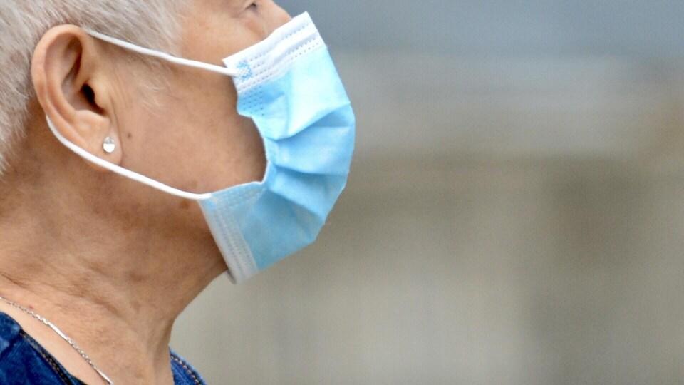 Une femme âgée portant un masque sanitaire.