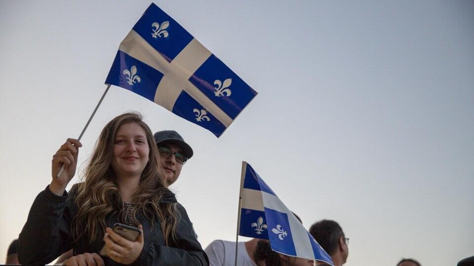 Des spectateurs brandissent un drapeau du Québec.