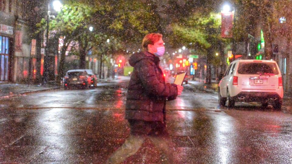 Un homme masqué traverse la rue sous la neige.