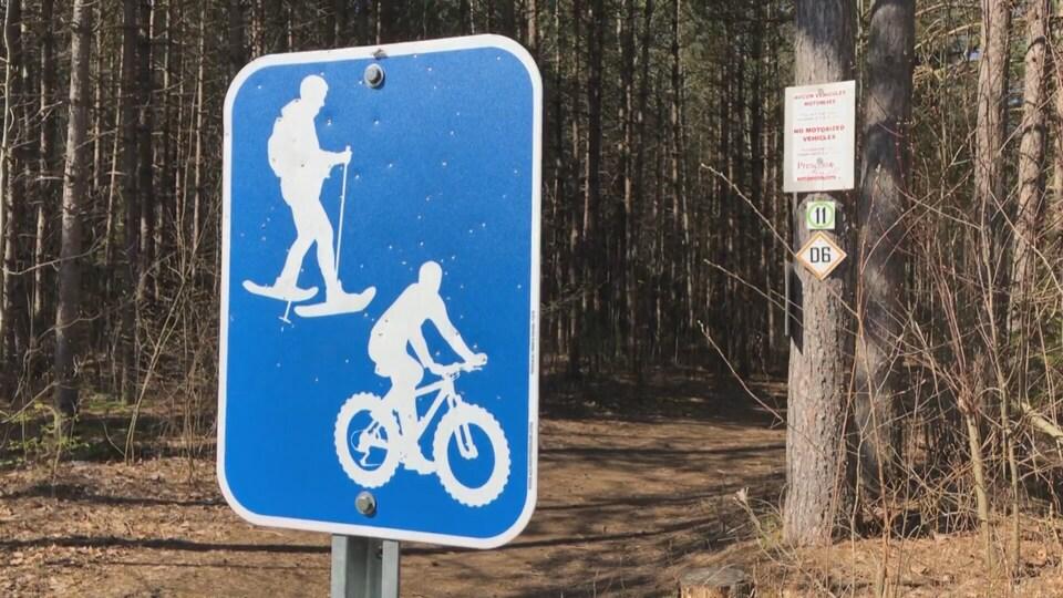 Affiche près d'un sentier sur laquelle on voit un cycliste et un homme en raquettes.