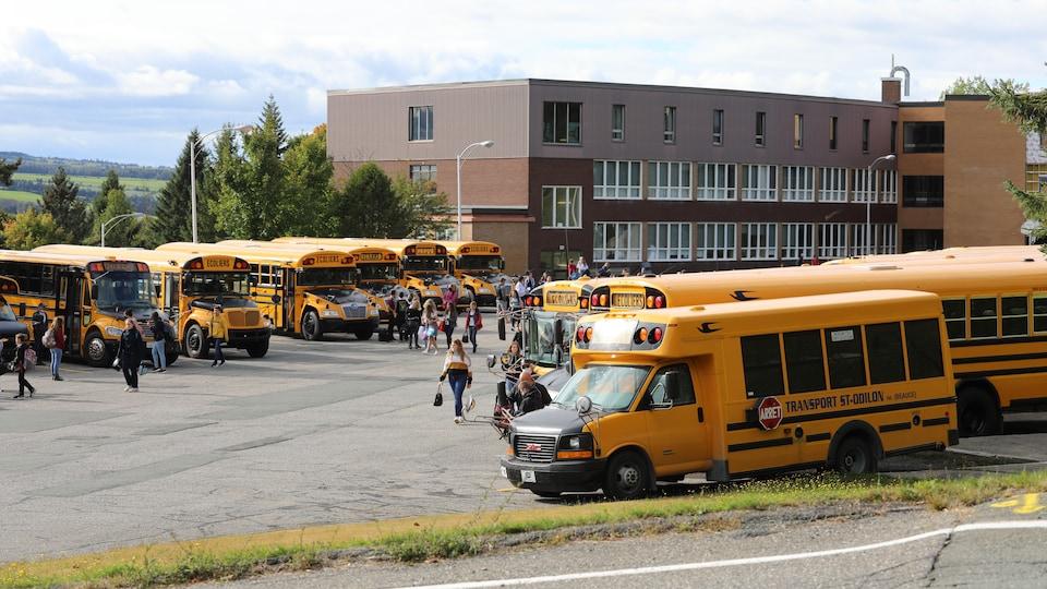 Un plan large d'une école secondaire avec des élèves et des autobus jaunes à l'avant-plan.