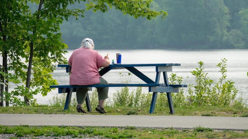 Une femme est assis à une table de piquenique près de la rivière.