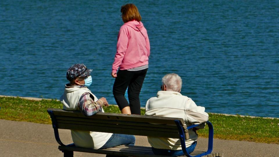 Des personnes en bordure d'un plan d'eau, dont deux assises sur un banc qui portent un masque.