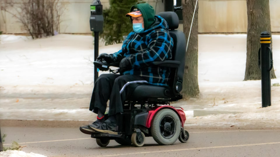 Un homme en fauteuil roulant sur le trottoir.