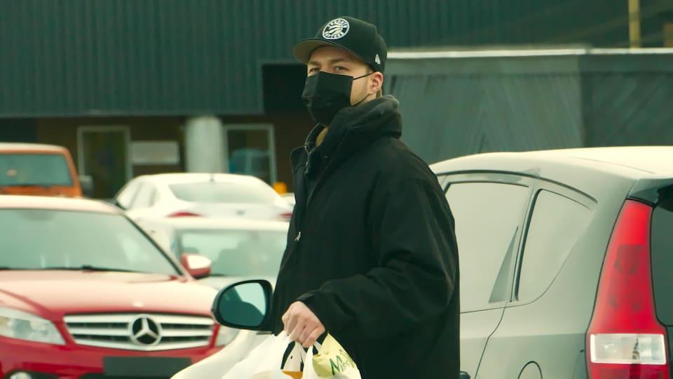 Un homme marche dans la rue avec un masque et une casquette. Il porte des sacs plastiques de course avec lui.