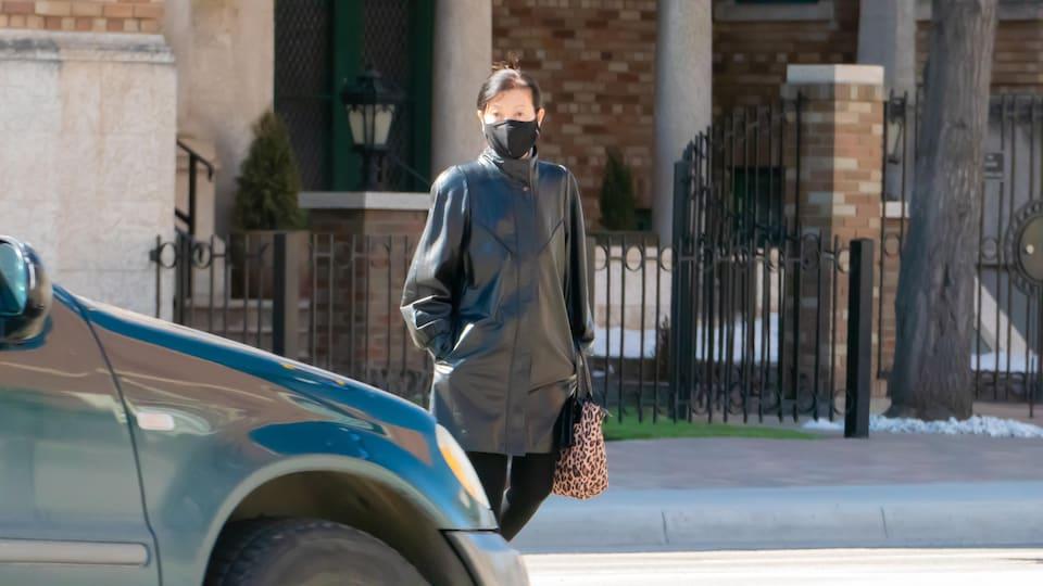 Une femme masquée traverse une intersection piétonnière devant une voiture immobilisée.