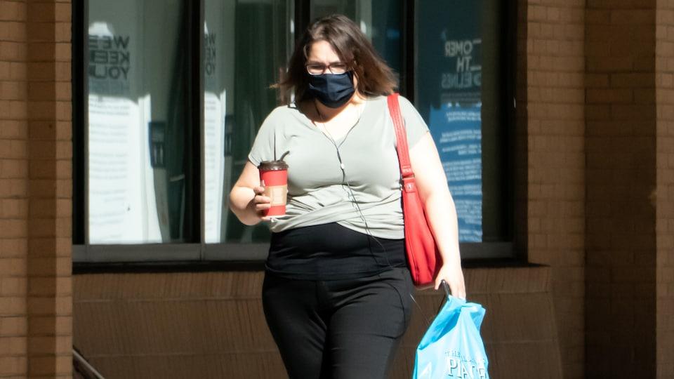 Une dame porte, café à la main, un couvre-visage.