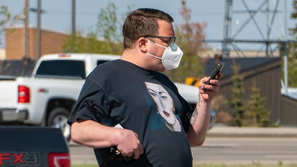 Un homme portant un masque regarde son téléphone dans la rue.