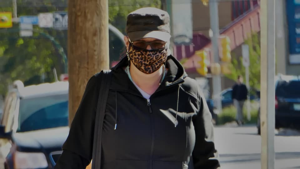 Une femme porte un masque dans une rue de Regina.