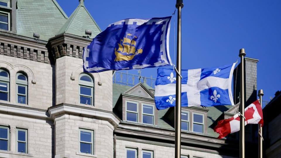 Les drapeaux flottent devant l'hôtel de ville de Québec.