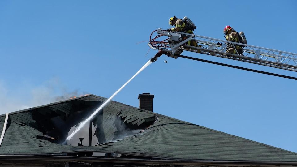 Des pompiers arrosent un toit en flamme.