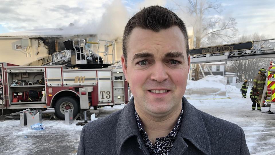 Robert McKee devant un camion des pompiers