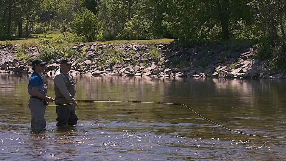 Un pêcheur et son enseignant dans une rivière.