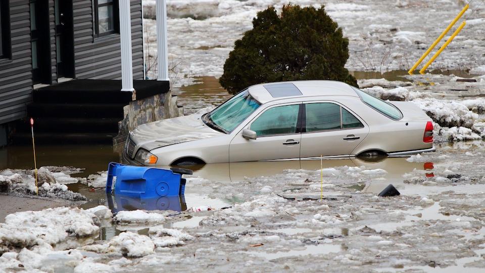 Une voiture est partiellement submergée par les eaux de la rivière Chaudière.