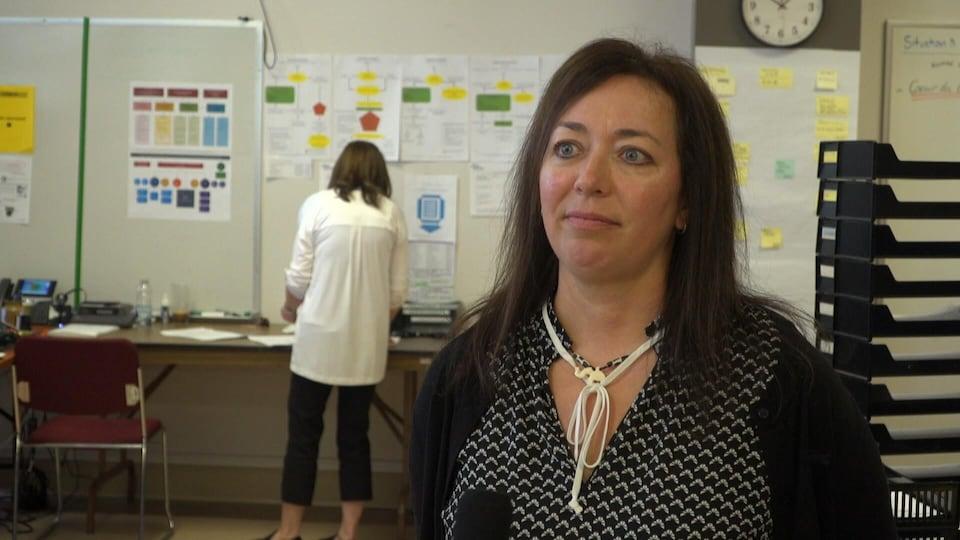 Isabelle Beaulieu accorde une entrevue dans un local. À l'arrière-plan, une femme, photographiée de dos, manipule des dossiers devant une table collée contre un mur.