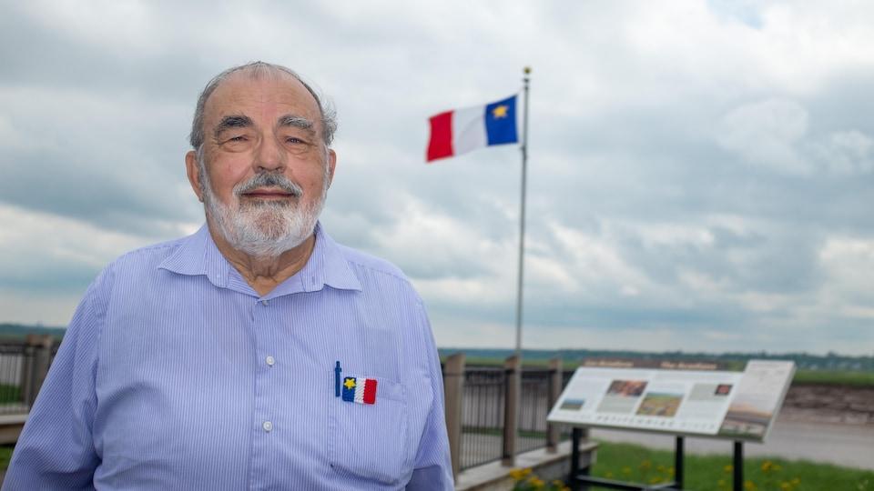 Un homme en chemise bleue avec un drapeau de l'Acadie au loin.