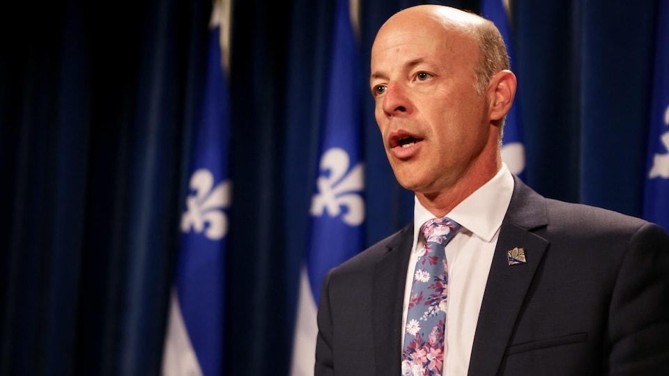 Joël Arseneau parle, devant des drapeaux du Québec.