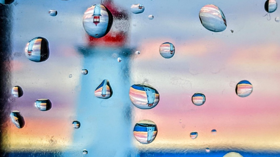 Des gouttes de pluie sur une fenêtre avec un phare en arrière-plan.