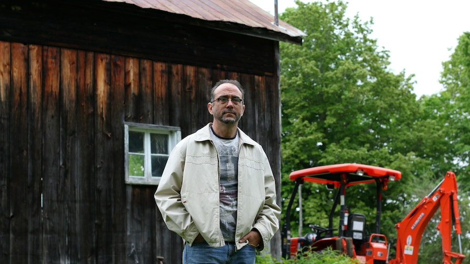 Stéphane Gendron pose devant un bâtiment agricole et un tracteur.