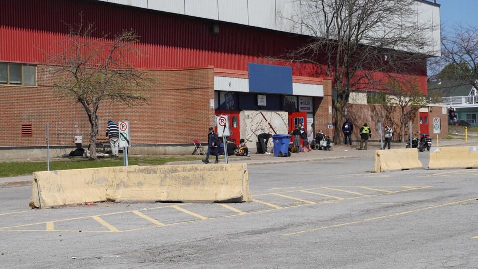 Des personnes dehors devant un bâtiment.