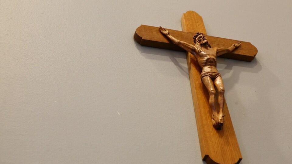 Photographie en contreplongée d'un crucifix en bois accroché sur un mur pâle