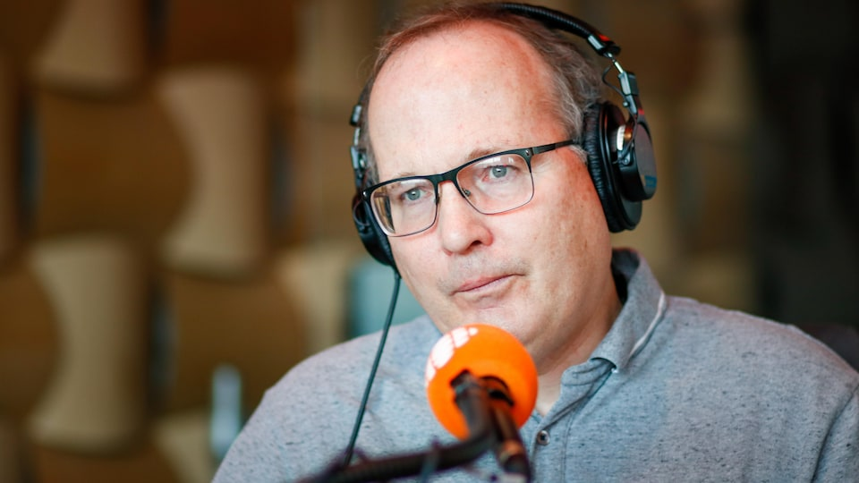 Un homme dans un studio parle à un micro.