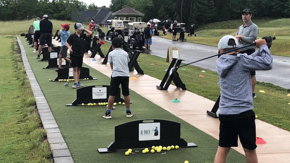De jeunes golfeurs s'élancent sur les tertres de départ d'entraînement.