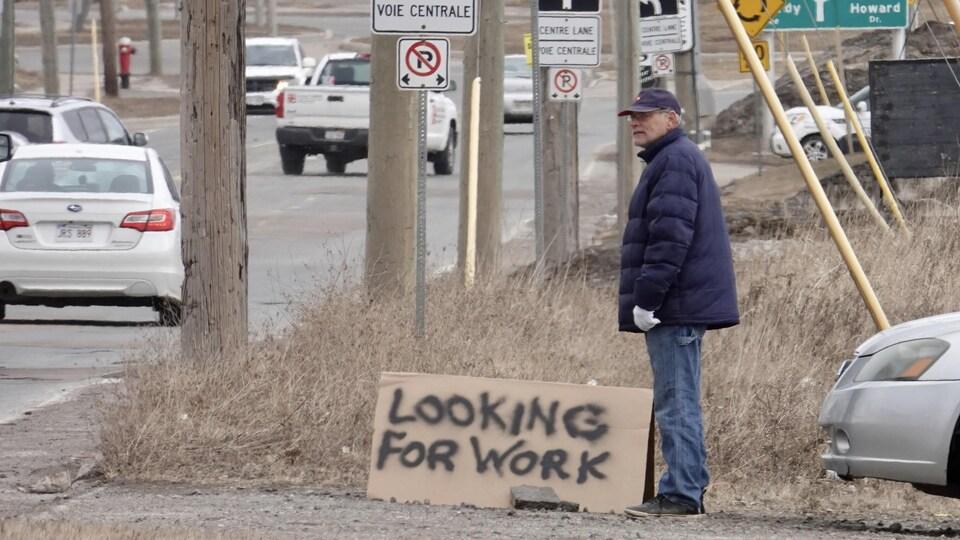 Un homme se tient debout sur le bord d'une route avec une affiche au sol, en carton, demandant de l'emploi.