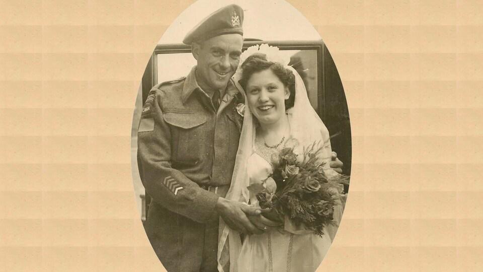 Photo de mariage. L'homme porte un habit militaire. La femme est habillée d'une robe nuptiale.