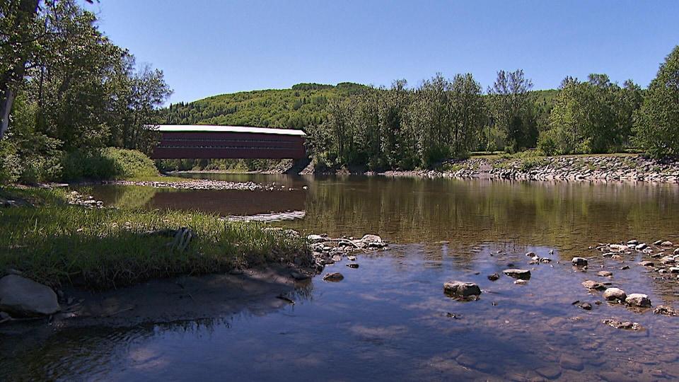 Rivière avec un pont couvert au loin.