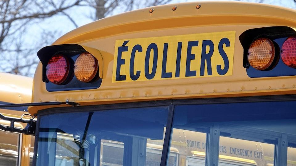 Gros plan sur l'inscription Écoliers d'un autobus scolaire.